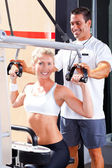 Personal trainer helping client in gym — Stock Photo