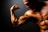 Bodybuilder posing on black background — Stock Photo