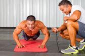 Homem de fitness e personal trainer no ginásio — Foto Stock