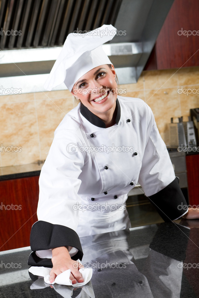 Female chef cleaning kitchen counter — Stock Photo #10674497