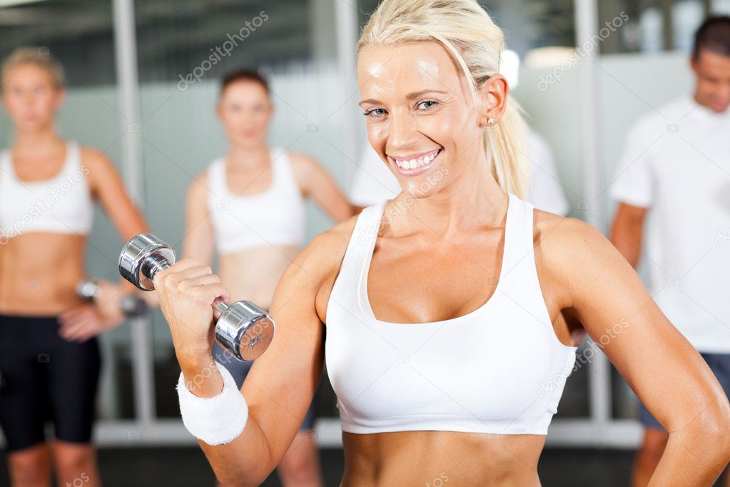 Young fitness woman doing dumbbell exercise in gym — Stock Photo #10679409