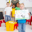 Kindergarten boy holding his painting in front of classmates — Photo