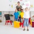 Preschool boy holding his painting in front of class — Stock Photo