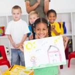 Proud kindergarten girl holding painting — Stock Photo