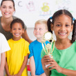 Preschool girl holding a trophy in front of classmates — Stock fotografie #10683249