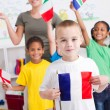 Foto de Stock  : Group of preschool kids and teacher with flags