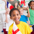 Stock Photo: Group of preschool kids and teacher with flags in classroom