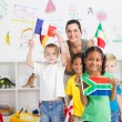 Foto de Stock  : Preschool kids and teacher with flags in classroom