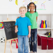 Two little classmates in preschool classroom - Stock Photo