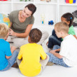 Preschool teacher teaching kids about globe — Stock Photo