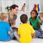Teacher reading book to preschool students — Stock Photo