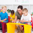 Preschool students and female teacher in kindergarten — Foto de Stock