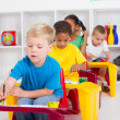 Group of four preschool kids in classroom — Stock Photo #10683747