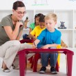 Preschool students and female teacher in kindergarten — Stock Photo