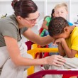 Stock Photo: Teacher comforting crying preschool boy