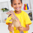 Stock Photo: Preschool boy playing with dinosaur
