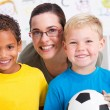Happy preschool teacher and two boys in classroom — Stock Photo