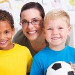 Happy preschool teacher and two boys in classroom — Stock Photo