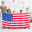 American preschool students and teacher holding a USA flag - Stockfoto