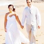 Groom and bride walking on beach — Stock Photo