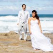 Groom and bride on beach rocks — Stock Photo