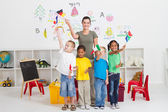 Reschool kids and teacher with flags in classroom — Stock Photo