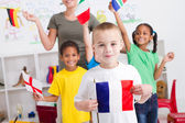 Group of preschool kids and teacher with flags — Stock Photo
