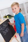 Preschool boy in front of blackboard — Stock Photo