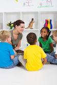 Nauczyciel czytania książki w wieku przedszkolnym — Zdjęcie stockowe