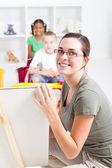 Beautiful young preschool teacher teaching in classroom — Stock Photo