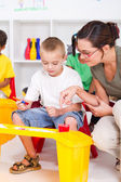 Kindergarten teacher and preschool students — Stock Photo