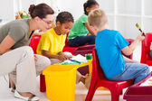Preschool students and female teacher in kindergarten — Stock Photo