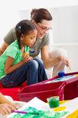 Caring teacher help preschool girl painting picture — Stock Photo