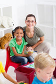 Happy preschool teacher and students — Stock Photo