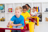 Group of four preschool kids in classroom — Stock Photo