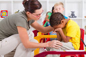 Teacher comforting crying preschool boy — Stock Photo