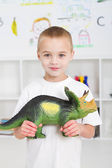 Preschool kid playing with dinosaur — Stock Photo