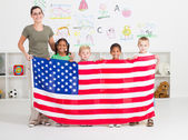 American preschool students and teacher holding a USA flag — Stock Photo