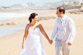 Newlywed couple walking on beach — Stock Photo