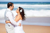 Newlywed couple hugging on beach — Stock Photo