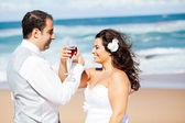 Novio y la novia bebiendo champán en la playa — Foto de Stock