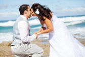 Newlywed couple kissing on beach — Stock Photo