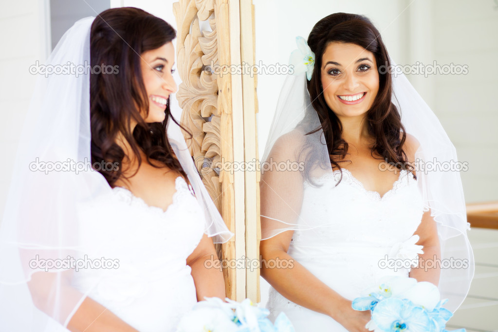 Happy bride looking into mirror — Stock Photo #10686039