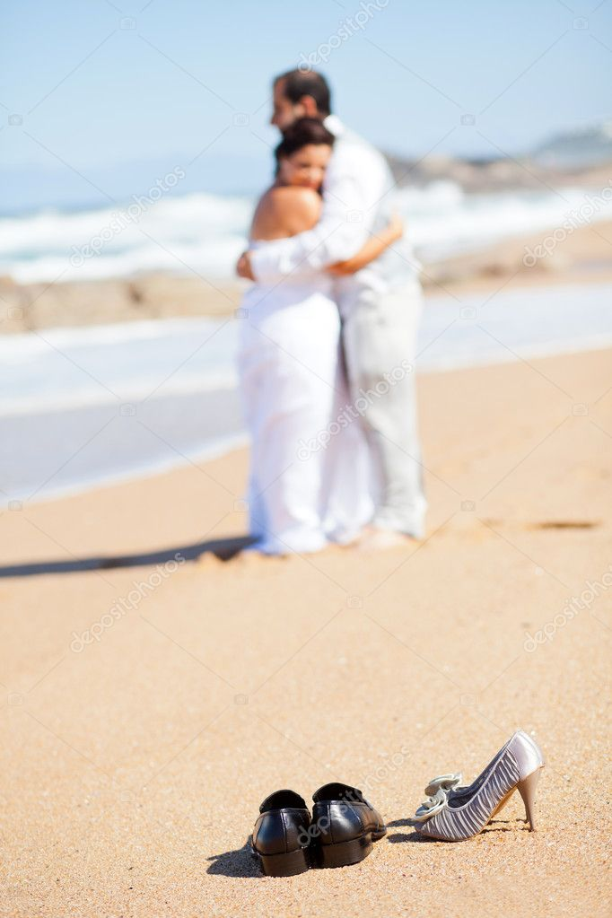 Bride and groom hugging on beach, focus on shoes — Stock Photo #10686089