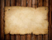 Old torn paper pinned by nails to grunge wooden wall — Stock Photo