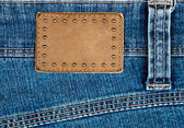 Blank leather jeans label decorated by rivets — Stock Photo