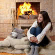 Happy teenage girl in winter clothes sitting fireside — Stock Photo #8394953