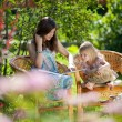 Girls reading book sitting in wicker chairs outdoor in summer da - Stock Photo