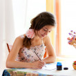 Girl writing at table by pen and ink indoor in summer day with s — Stock Photo