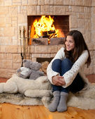 Happy teenage girl in winter clothes sitting fireside — Stock Photo